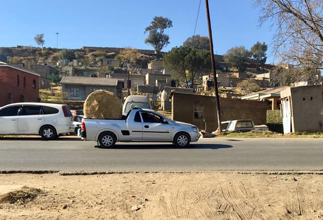 Hauling a round bale off near my guest house. — in Maseru, Lesotho.