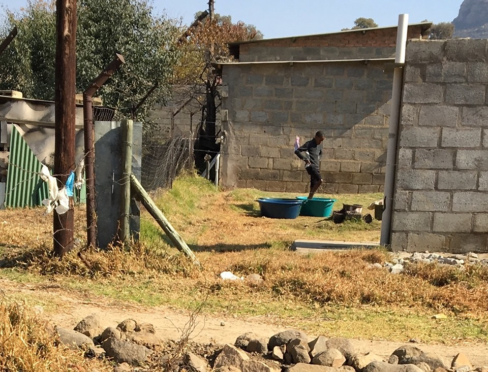Laundry day. The bucket the young man is standing/stomping in is full of clothes and soapy water. He is the washing machine. Next is the rinse cycle, followed by the dryer (sun). — in Maseru, Lesotho.