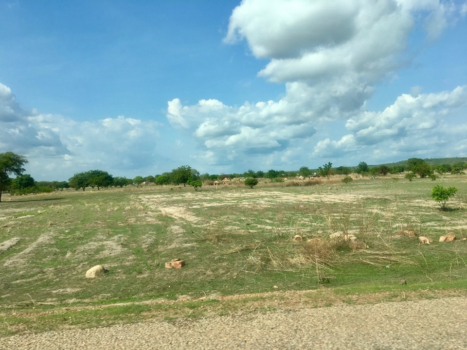 Lots of open fields. This one has a family compound in the background. — in Ghana.