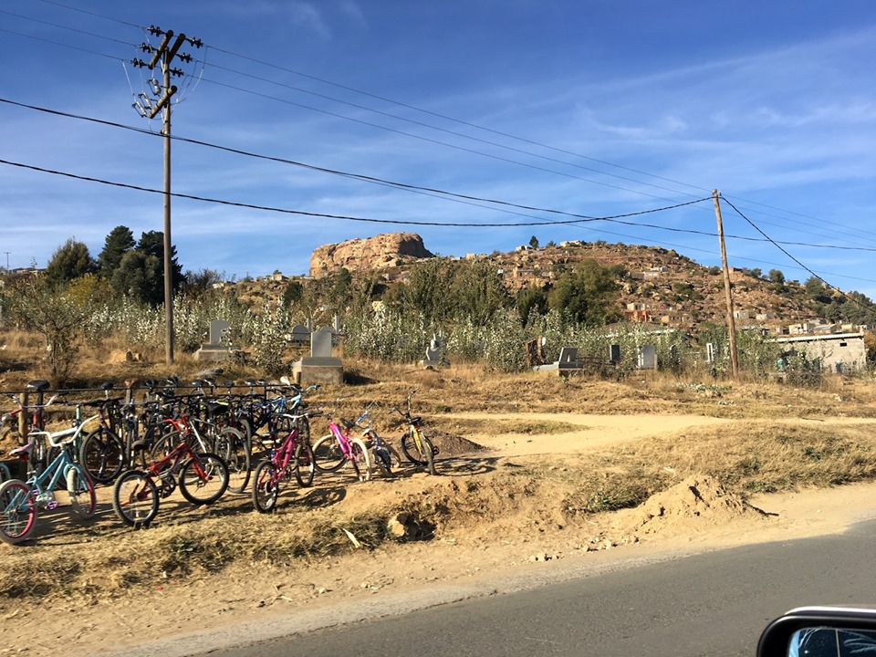 Street scene. Bikes for sale in the foreground, overgrown cemetery in the mid-ground, and houses built into the hill/mountain in the background. — in Maseru, Lesotho.