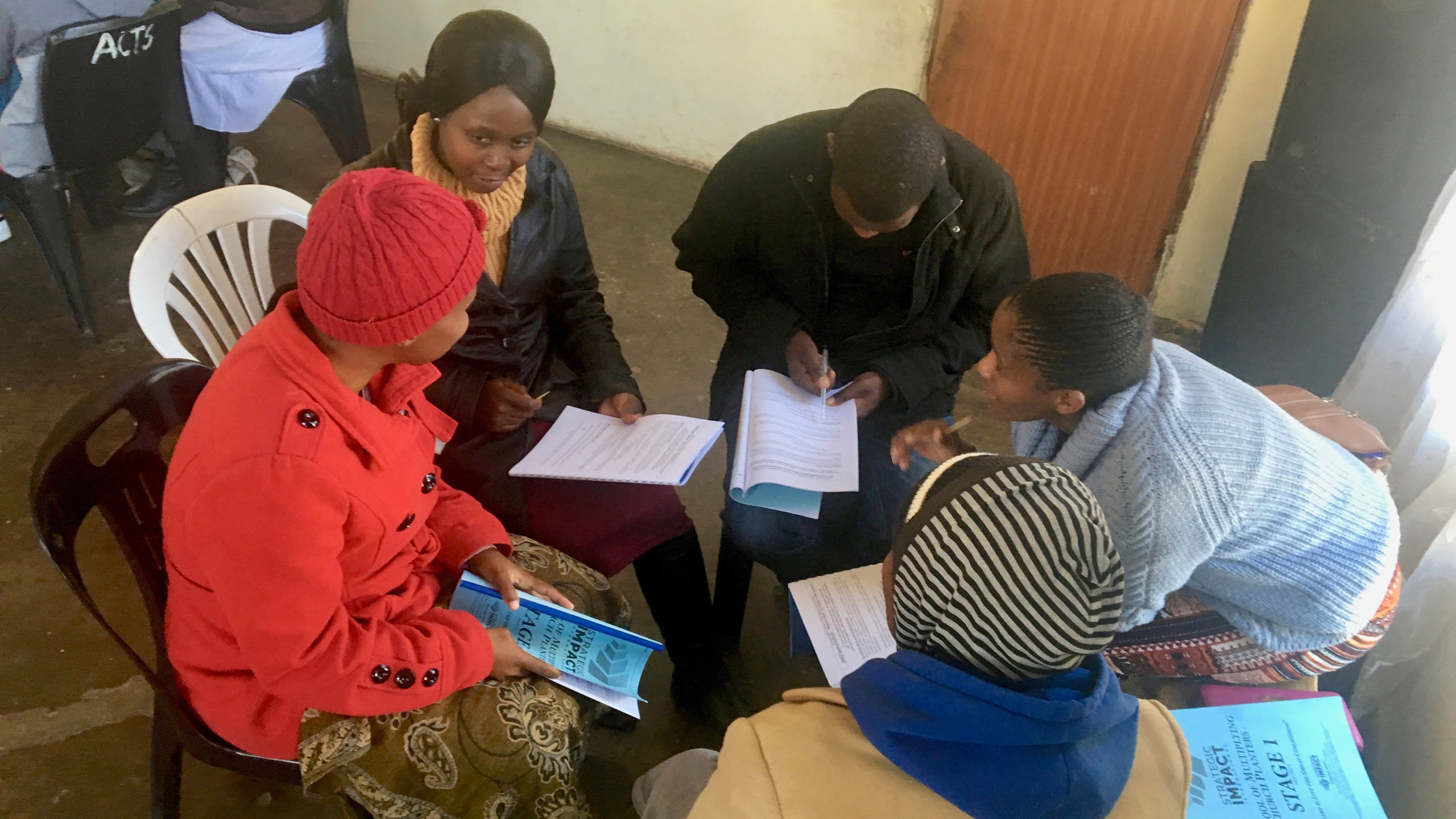 Alice Khoabane helping some new enrollees in the School of Multiplying Church Planters through their first exercise.