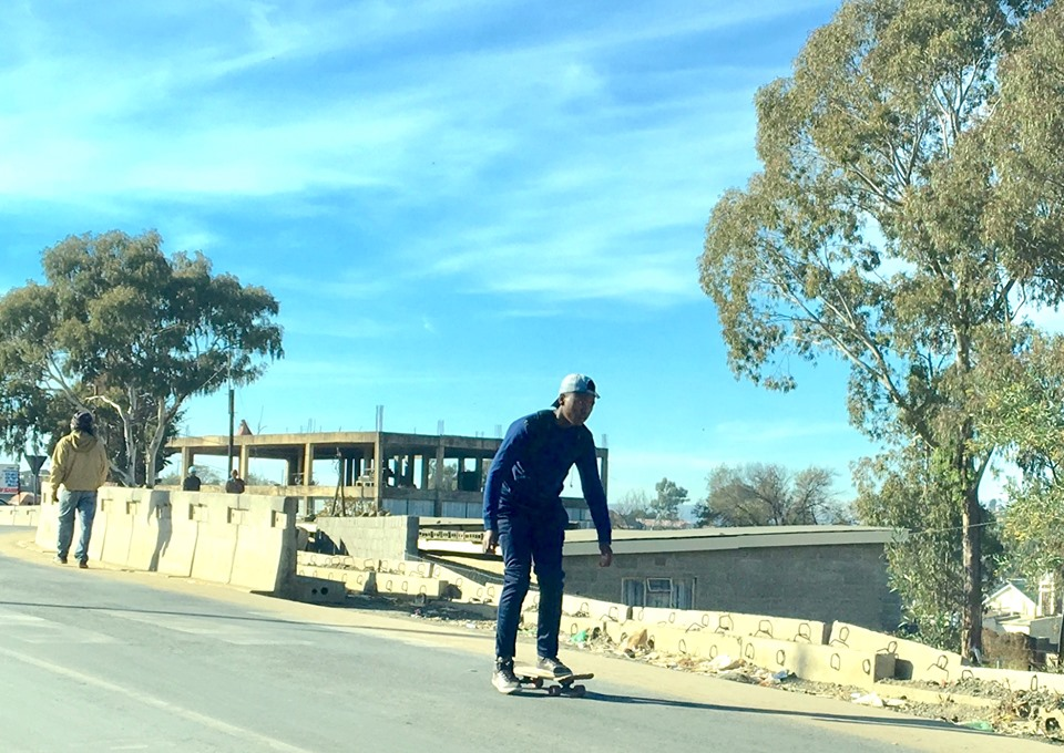 Sk8boarder rolling down the new pavement. (did I do that right? With the '8'?) — in Maseru, Lesotho.