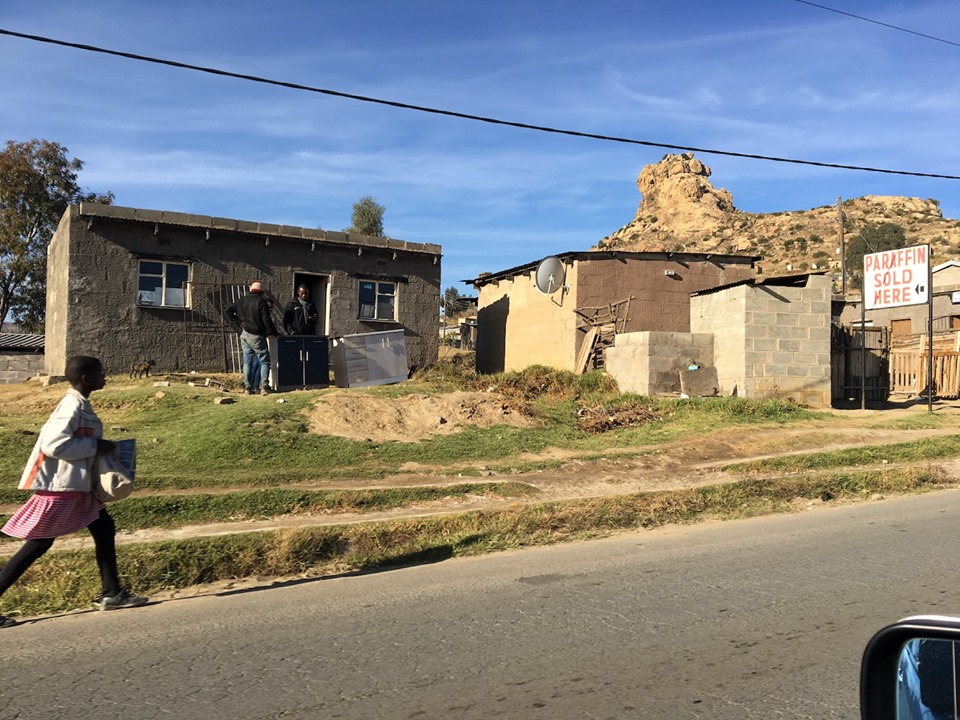 """Street scene. The """"Paraffin"""" sign is for heating oil used in cooking and heating - like the small red heaters you may have seen in the church in some of the other photos. — in Maseru, Lesotho."""