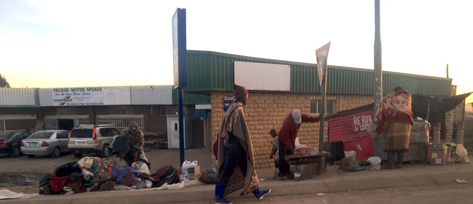 Street scene. Man cooking some food to sell by the yield sign. Another man in the foreground and woman on the right are wrapped in the traditional way they wear blankets here. Lady on the left is closing up her clothes shop for the day. — in Maseru, Lesotho.
