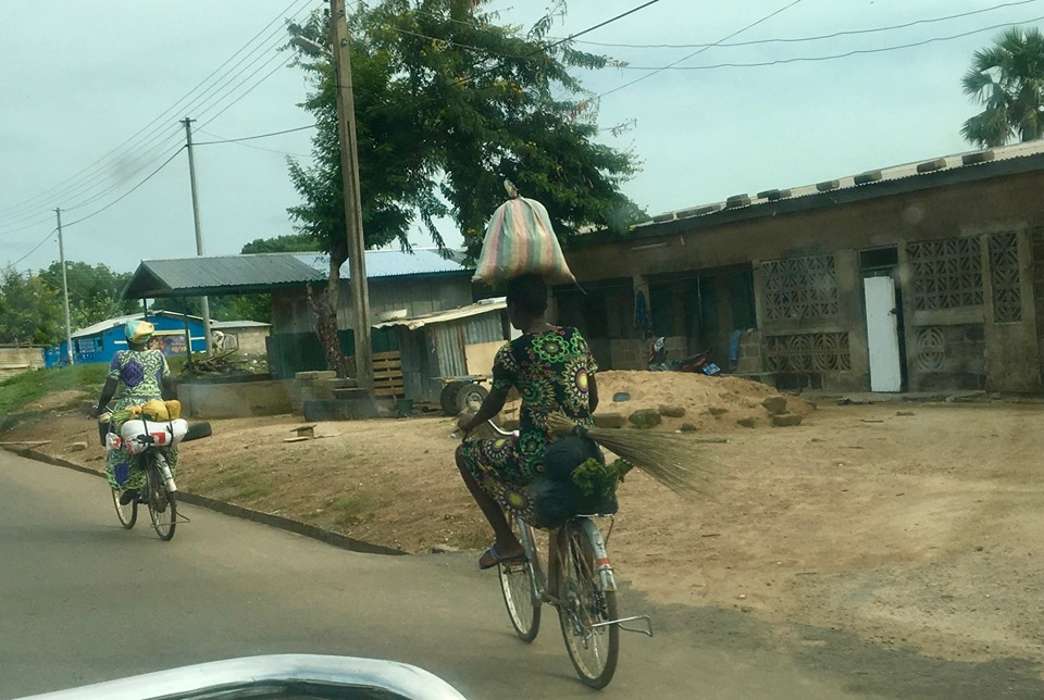 Bag balanced on the head, riding a bicycle, broom mounted on the rear. Some people also bike with all this and a child strapped to their back. — in Navrongo.