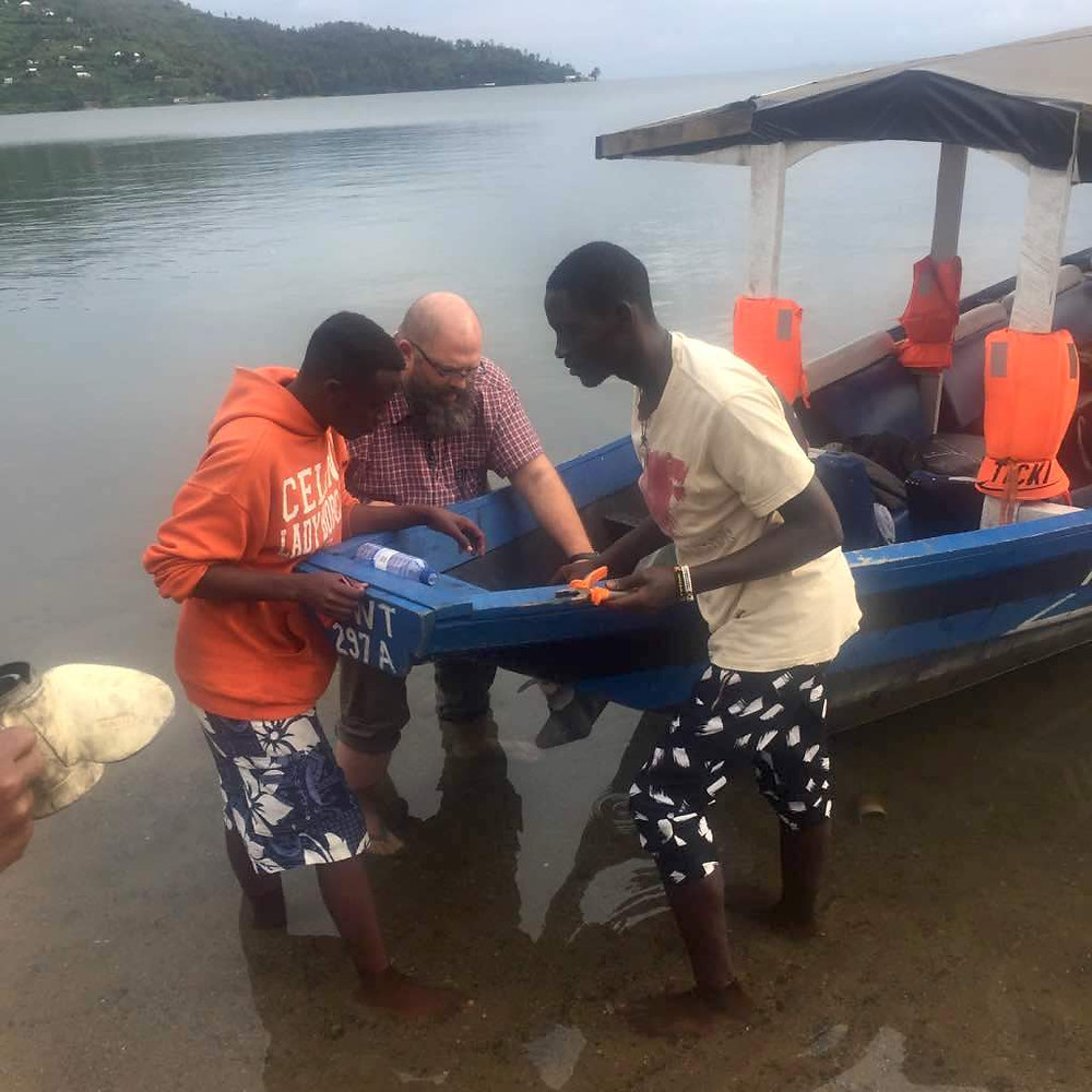 Dustin helping change a boat propeller on Lake Kivu