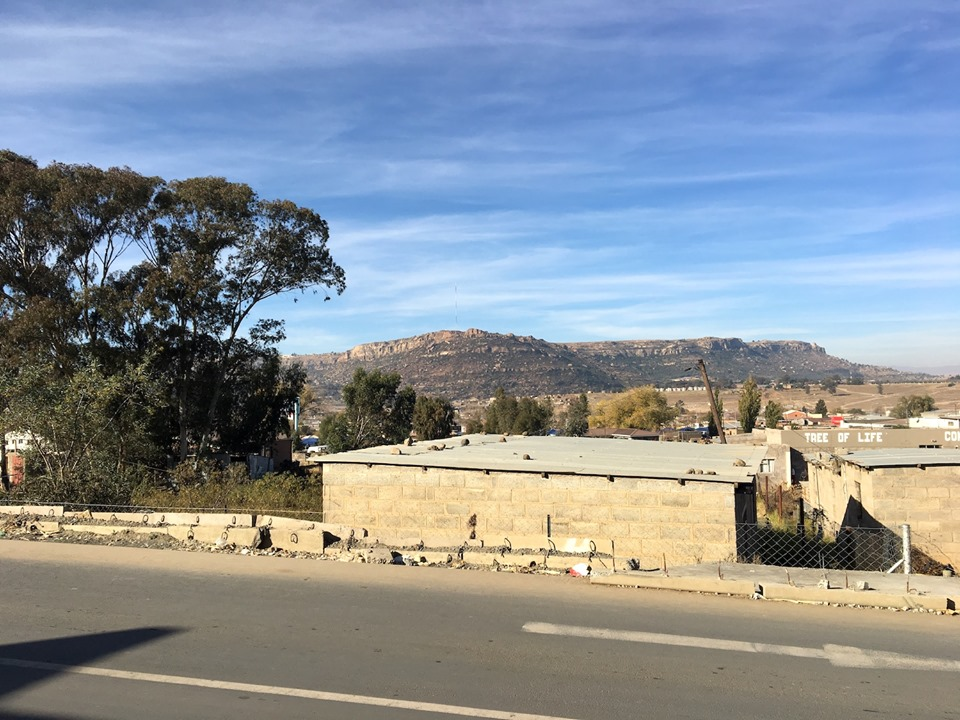Waiting for my ride. The rocks on the top of the roof keeps them from rattling in the wind. — in Maseru, Lesotho.
