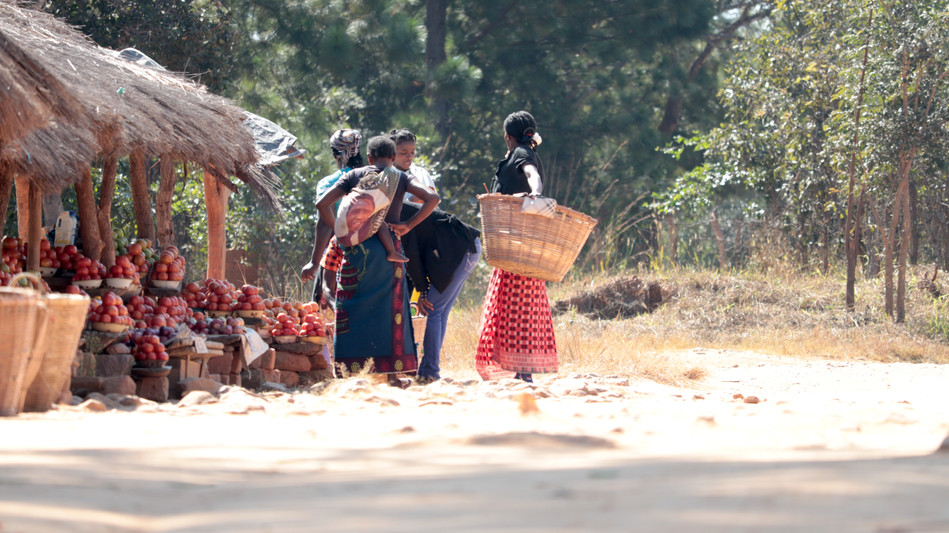 Ladies buying their supply of fruits and vegetables at the stand.