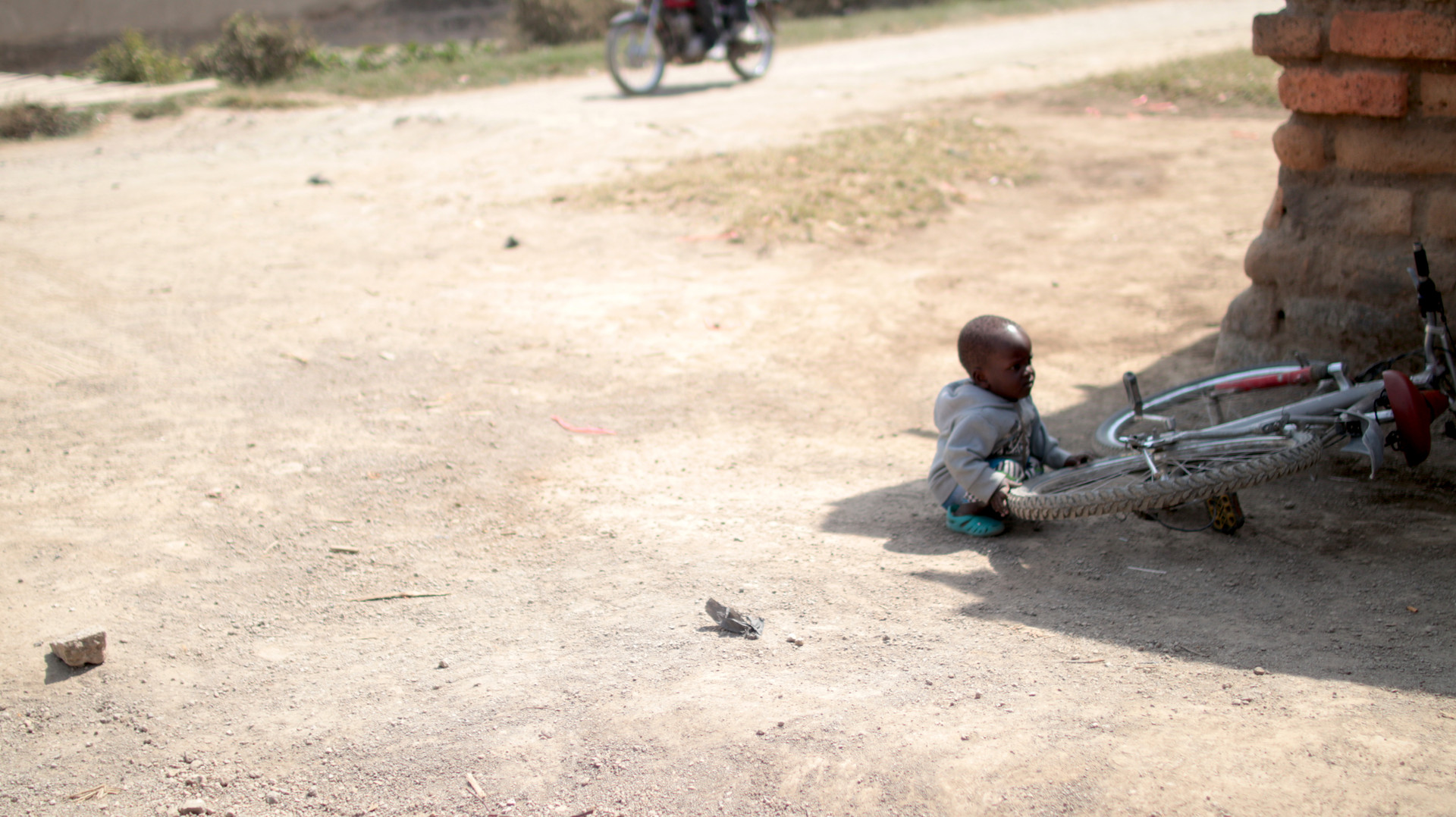 A young kiddo playing with a bicycle in the streets of Mbeya