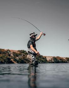 Angler wearing waders fly fishing
