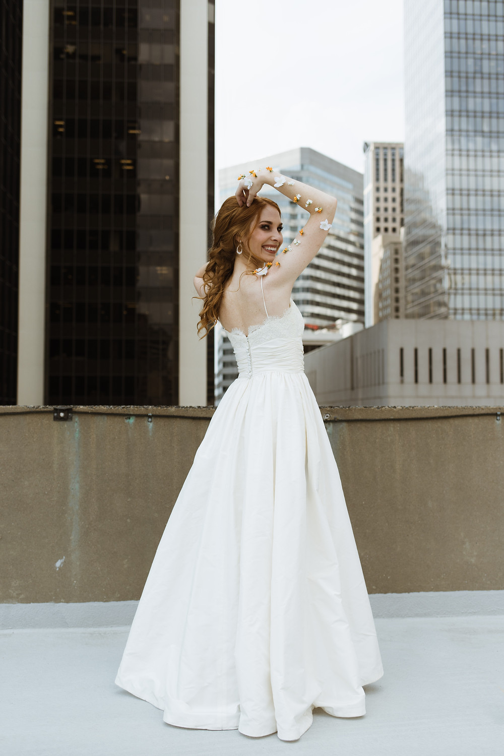 Model bride with uptown charlotte city skyline behind with hair and makeup done
