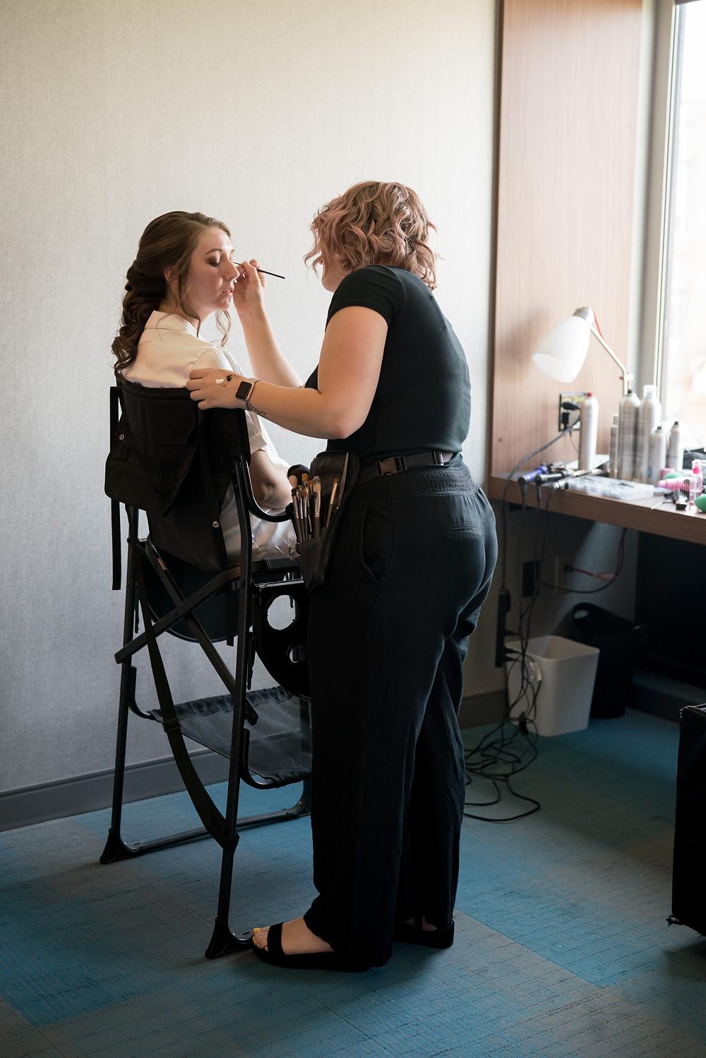 photo of megan oliveri working on a bride's makeup for her wedding in durham north carolina