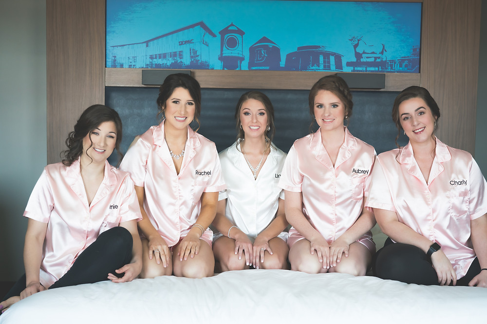 Bride and bridesmaids sitting on the hotel bed with etsy silk pajamas in durham north carolina
