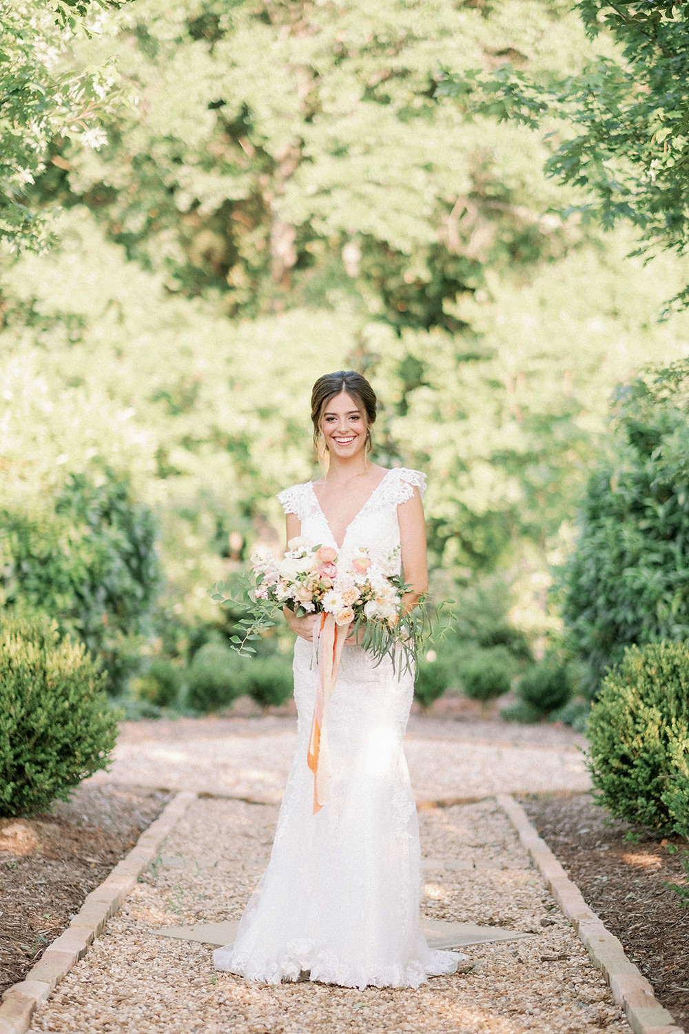 beautiful bride holding a bouquet of flowers in a garden by becca jones photography