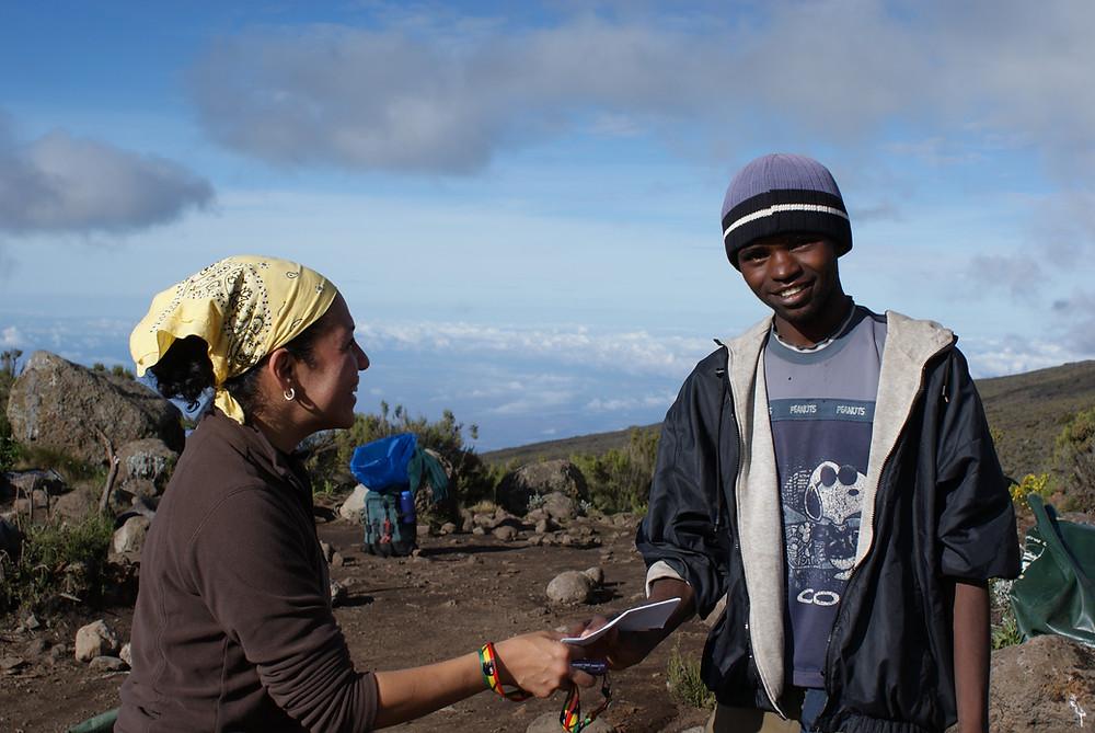 Climber handing a tip envelope to a porter