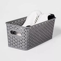 White tennis shoes inside gray plastic weave basket