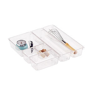 Clear plastic drawer organizers in various sizes holding kitchen utensils