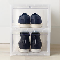 Two pairs of shoes neatly stacked via plastic bins