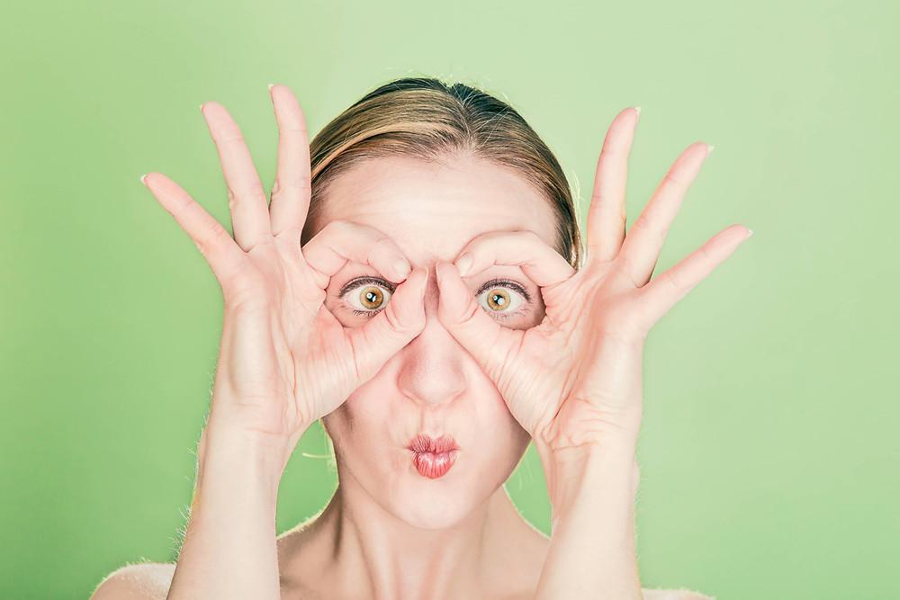 femme qui fait un rond sur ses yeux avec ses doigts