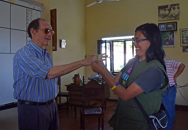 "Angie placing ""Fly Free Parrot"" wrist bands on manger of Estancia Hermosa, Dr. Francisco Varela"