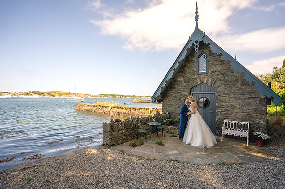 A wedding couple beside a boathouse at a Northern Irish Wedding