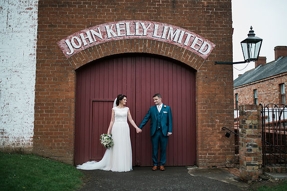 A wedding couple stand in front of an old irish barn door