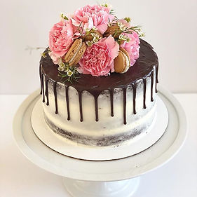 Naked drip cake topped with flowers and