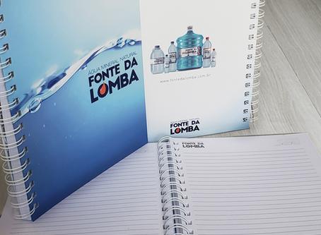 Clientes e Amigos Fonte da Lomba recebendo caderno personalizado da marca.