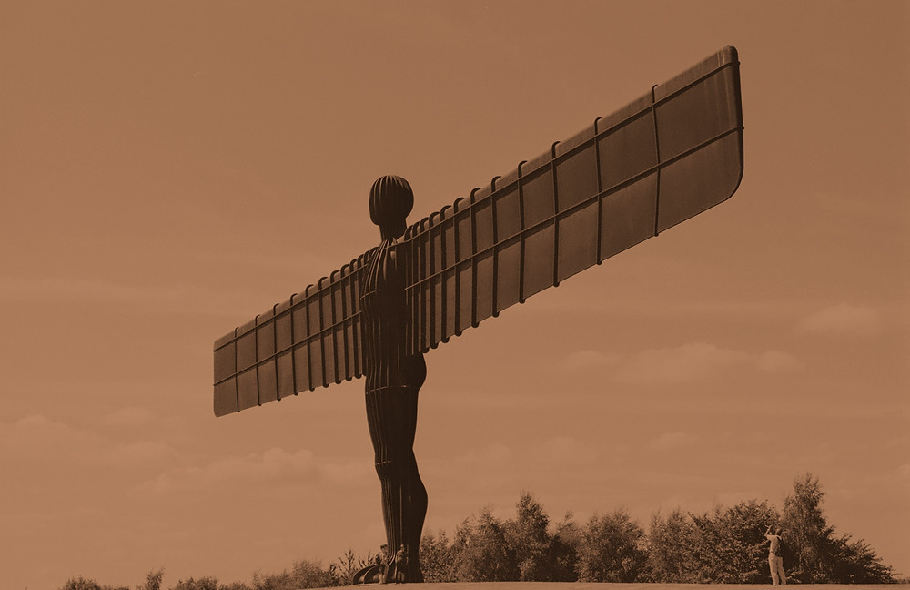A photographs of the Angel of the North in Gateshead. A large metal figure stands on a hilltop with two outstretched rectangular wings.