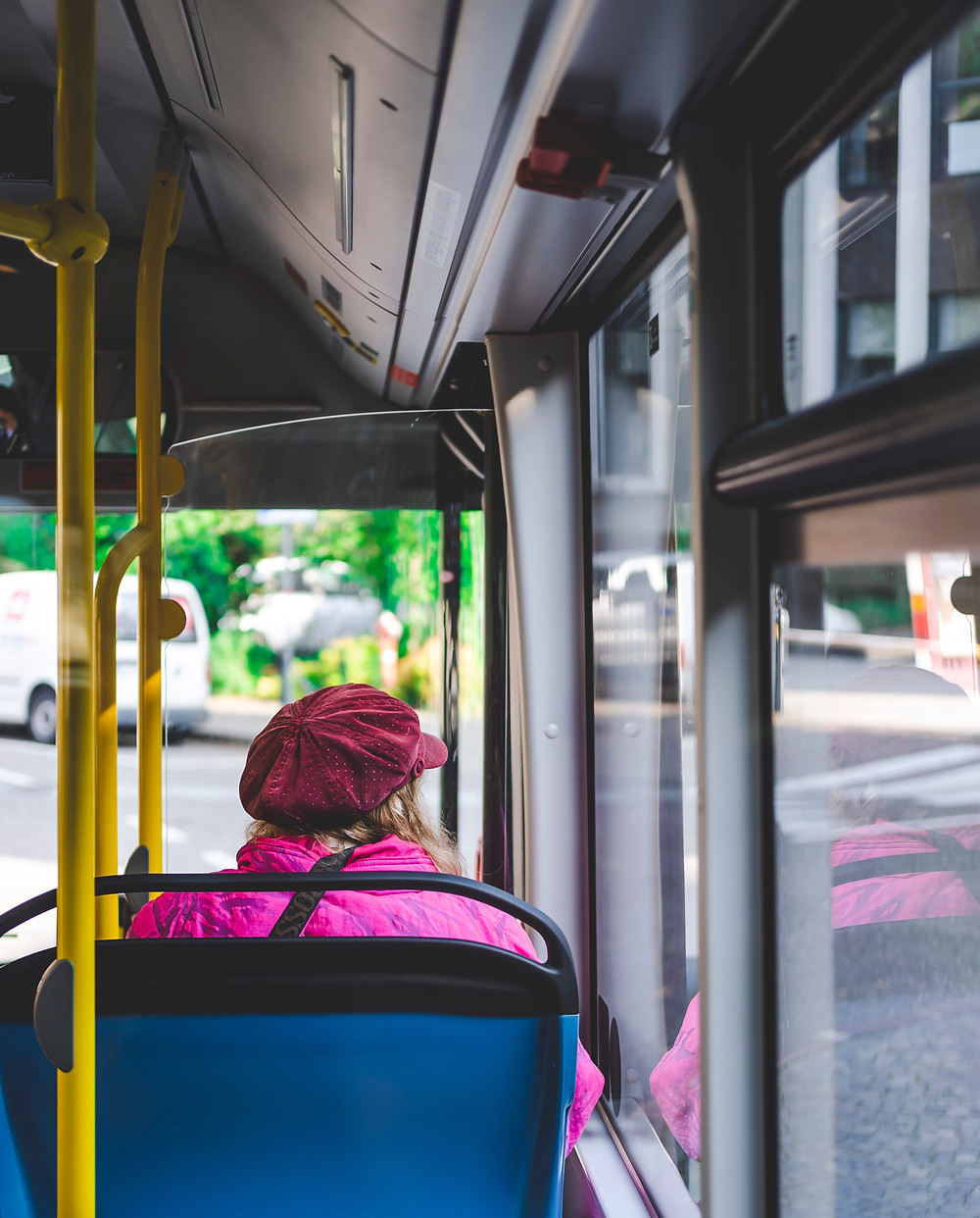 View of the back of a lady sat on the bus, wearing a cap and pink jacket looking out the window.