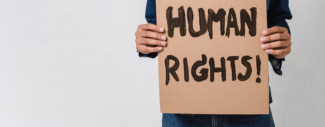 A man holding a cardboard sign saying 'Human Rights'