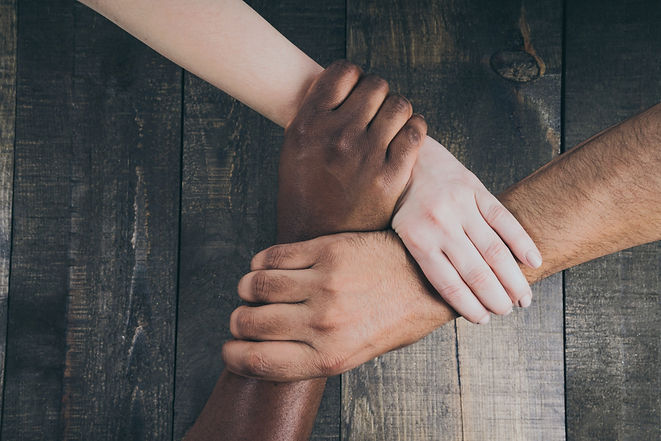 Three people's hands linked together by holding the wrist of the next person