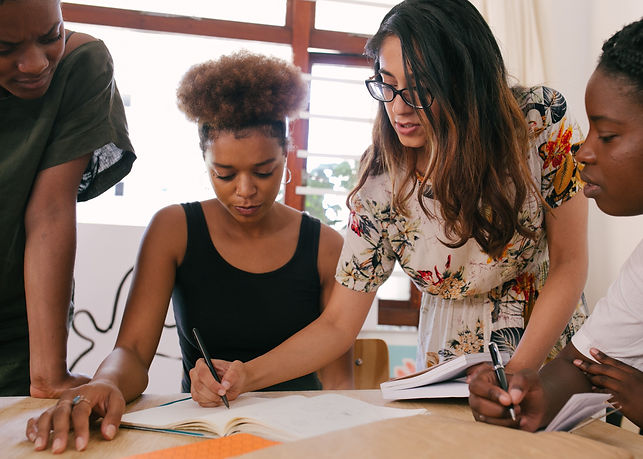 A group of women writing ideas on flipchart paper on a table