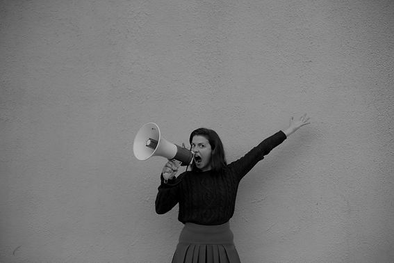 A woman shouting into a megaphone with her arm in their air