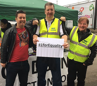 Three men from NUFC Fans Foodbank standing in front of the stadium holding a sign saying #1forEquality