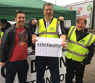 Three men from Newcastle United Fans Foodbank standing together holkding a sign saying #1forEquality