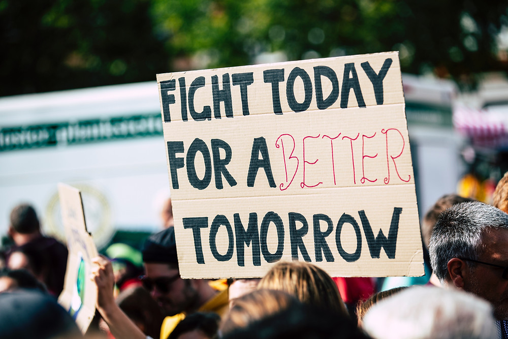 """Heads of a protest crowd, one cardboard placard reads """"Fight today for a better tomorrow"""""""