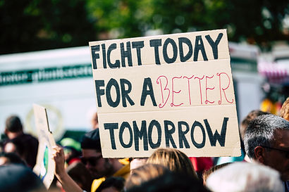 A group of people holding a sign saying 'Fight Today for a Better Tomorrow'