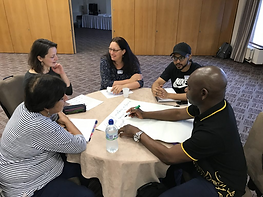 A group of people sitting discussing ideas around a table at the Sanctuary in Politics workshop