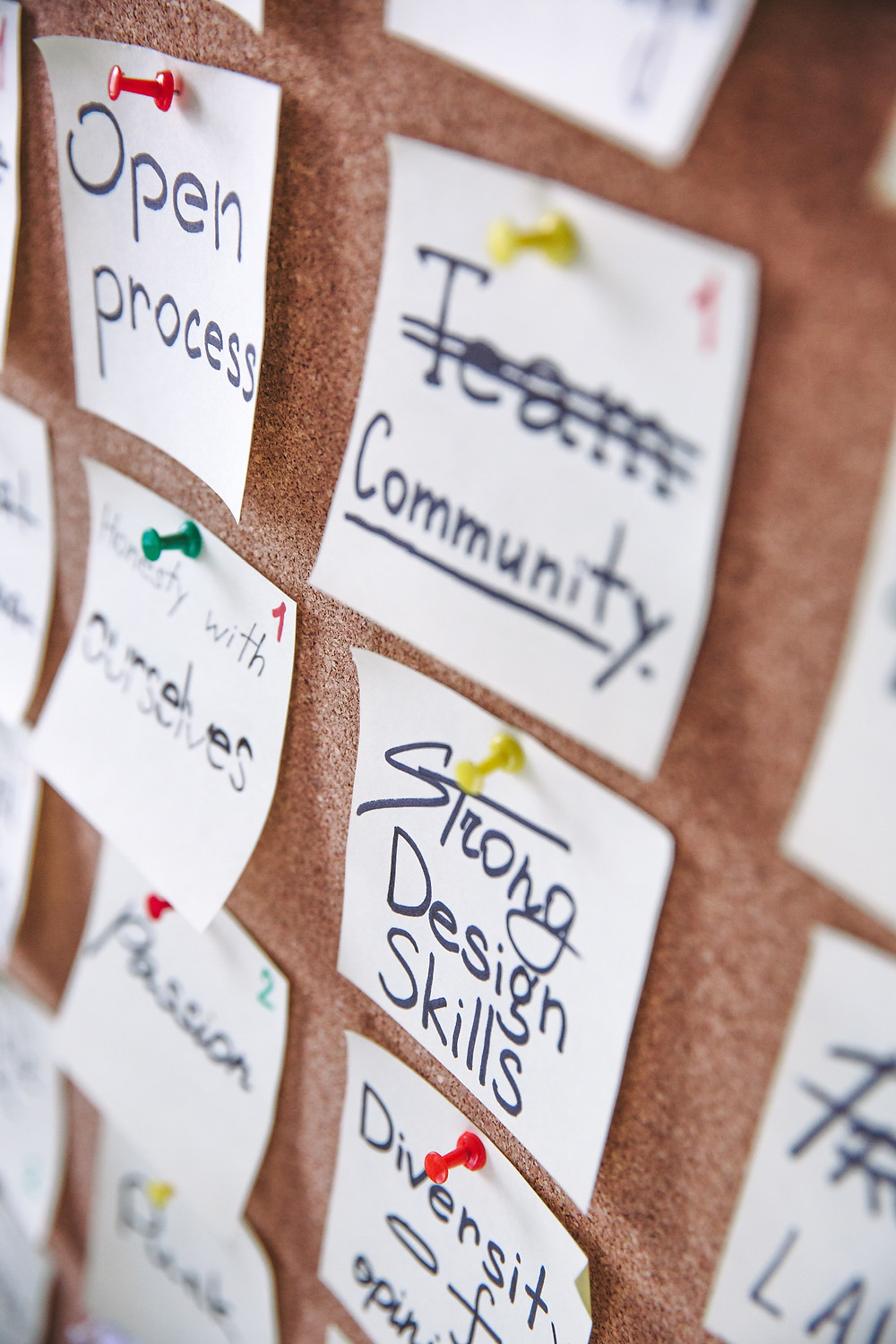 """A series of post it notes pinned to a cork board, reading """"Open process"""", """"community"""", """"Strong design"""", """"Ourselves"""""""