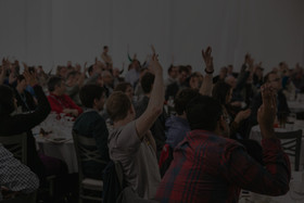 A room filled with people, half of whom have their hands in the air
