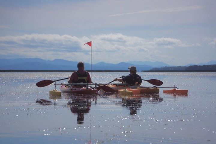 Two paddlers in adapted kayaks