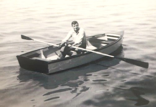 Young man rowing a rowboat around 1950.
