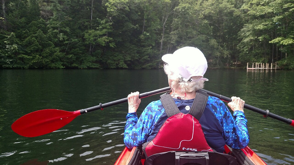 Older adult kayaking with adaptive paddle