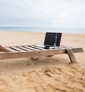laptop-with-earphones-on-beach-chair-wit