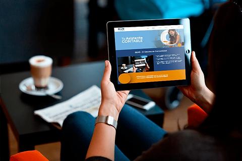 Mujer sosteniendo tableta electronica, tasa de café y periódic