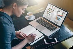 mujer escribiendo en diario con laptop