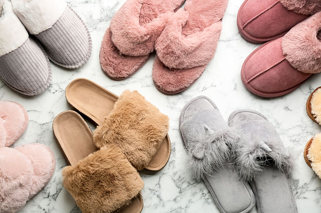 Many different soft slippers on white ma