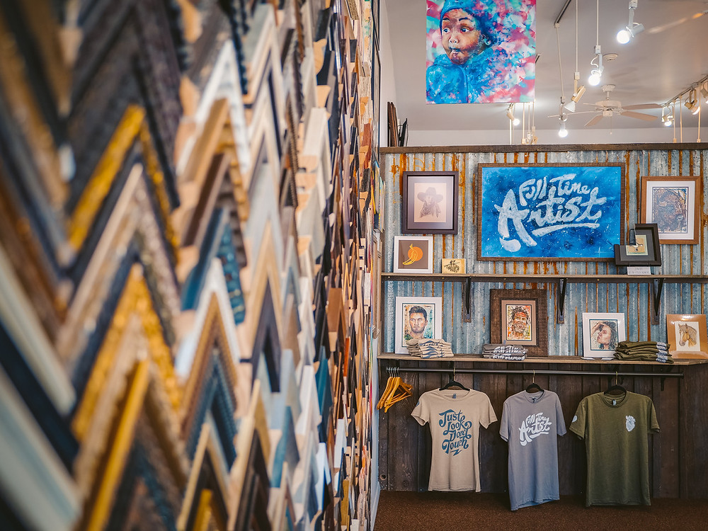 A wall of framing material samples on the left; in the distance are multiple shelves with examples of artwork, and tshirts for sale