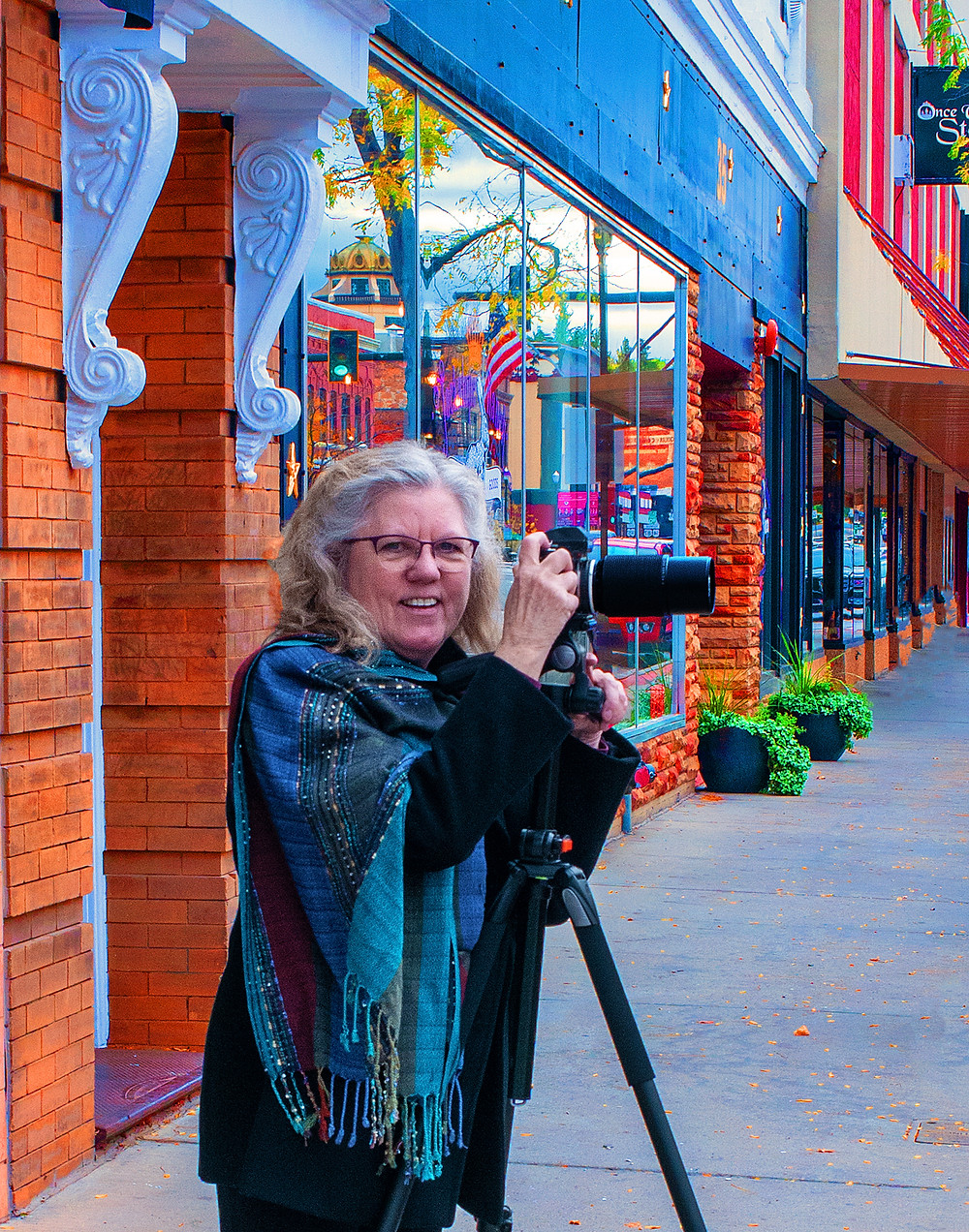 Becky smiles at the camera while holding her own camera on a tripod. She is wearing a blue shawl and standing in front of Frackelton's Restaurant.